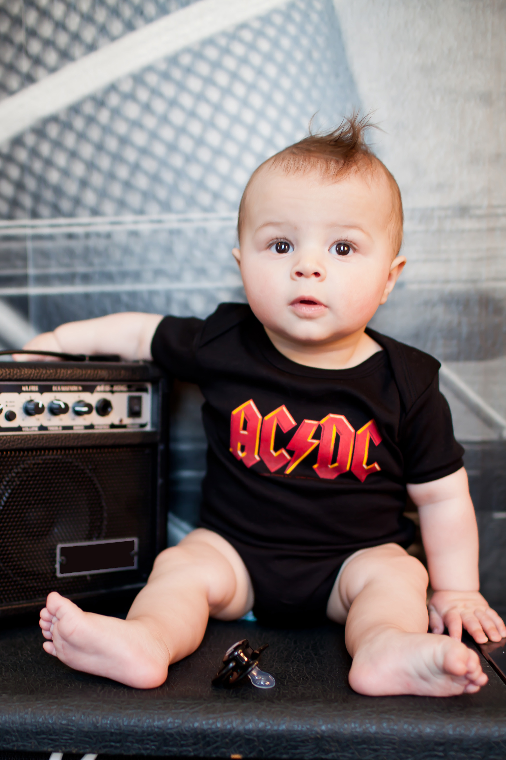 AC/DC Baby Onesie sitting on guitar amp